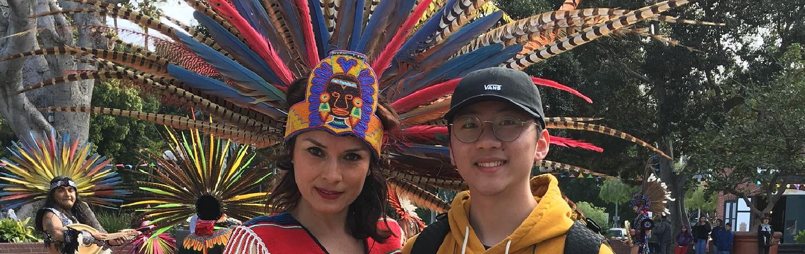 A woman with an elaborate costume with colorful feathers posing with a tour goer.